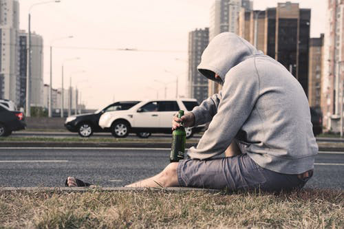 man sitting on curb drinking alcohol