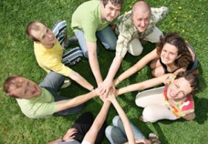 group of people with hands in center of circle