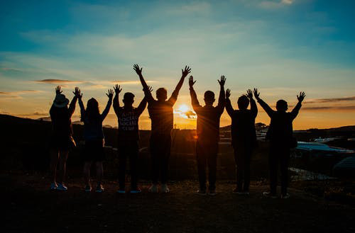group of people celebrating with arms raised