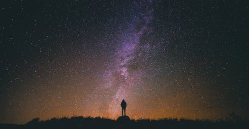 silhouette of person against the milky way star galaxy