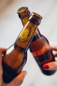 two beer bottles being toasted