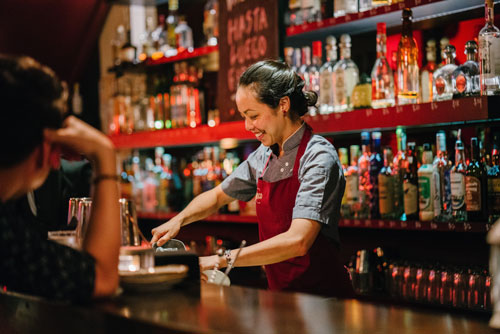 bartender in apron serving drinks
