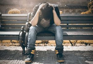 stressed young man on park bench