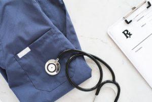 stethoscope laying on scrub uniform top near prescription pad