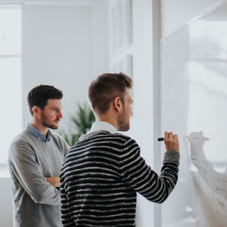 men writing on white board