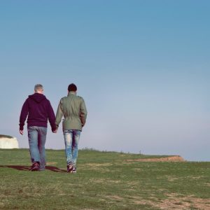 couple holding hands and walking outdoors