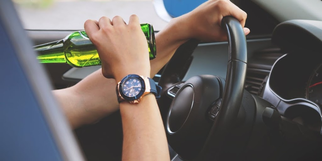 person driving car and drinking beer from green beer bottle