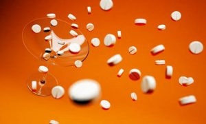 cocktail with tablets on orange background