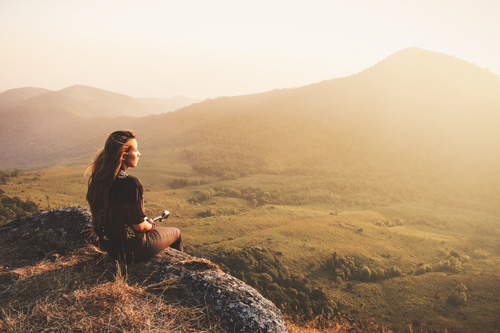 girl sitting on hill during sunset