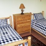 two twin beds with blue and white comforters inside client condo - English Mountain Recovery