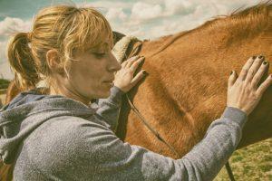 woman petting tan horse - holistic