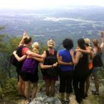 women on hike with arms around each other - English Mountain Recovery