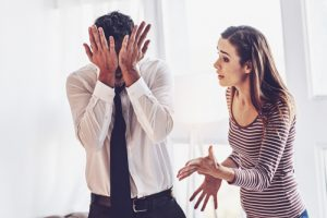 man pressing heels of his hands into his eyes with upset woman making hand gestures - toxic relationships