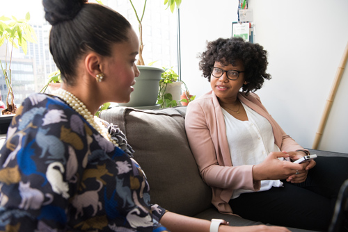 two beautiful African American women talking on couch in office - cognitive behavioral therapy