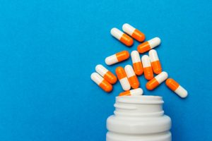 orange and white capsules spilling out of bottle on bright sky blue background - adderall