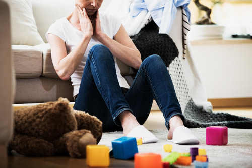 overwhelmed woman sitting on floor in living room with children's toys - functioning alcoholic