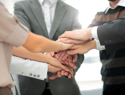 group of people with hands stacked in huddle