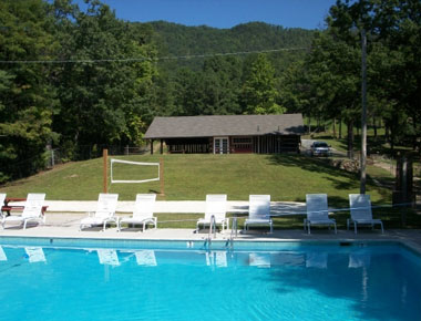 Outdoor pool with chairs and volleyball court in background - English Mountain Recovery