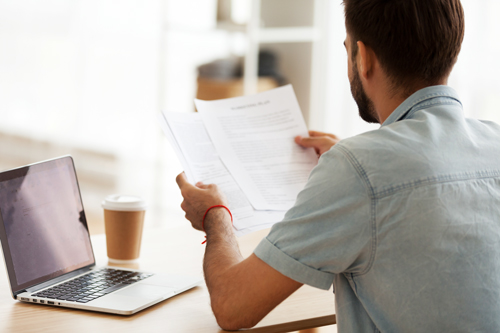 man reading papers in front of laptop - family medical leave act