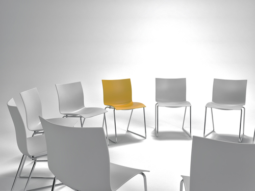 empty white chairs set up in a circle, with one yellow chair - SMART Recovery