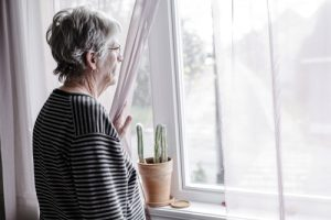 senior woman looking out the window - senior citizens
