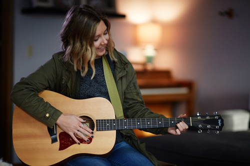 young woman playing acoustic guitar at home - creative arts