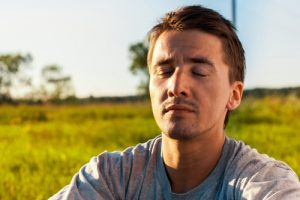 man outside with eyes closed meditating - mindfulness