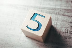 wooden block with the number five painted in blue - myths
