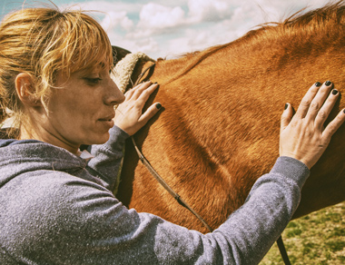 woman petting tan colored horse
