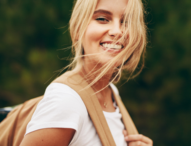 pretty smiling young blonde woman wearing backpack