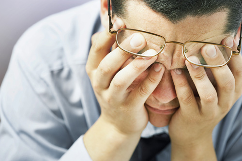 closeup of businessman with face in hands - stress and addiction recovery