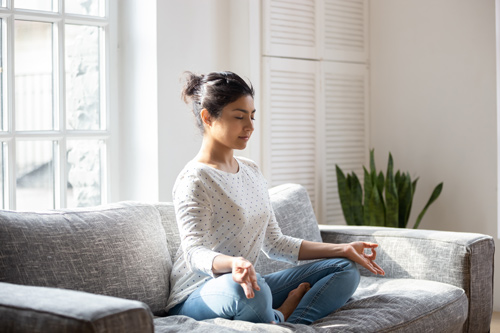 pretty young woman sitting cross-legged on couch at home, meditating - types of meditation
