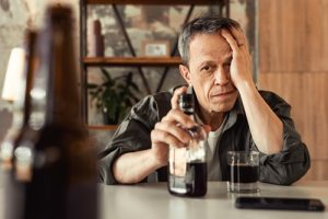 senior man drinking alcohol at home - binge drinking
