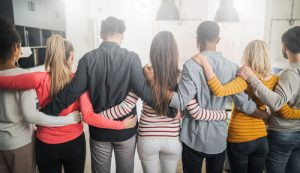 group of people with arms around each other - viewed from behind - 12-Step