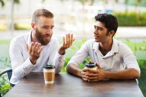 two men talking over coffee outdoors - sponsors