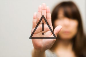 black triangle with exclamation point against woman holding out her hand in stop gesture - relapse warning signs