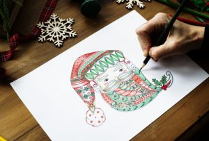 closeup of an adult hand using colored pencils to draw a Santa face on white paper - holiday season
