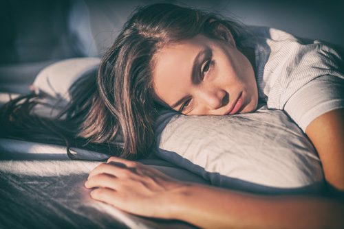 sleepy or high looking woman laying in bed - tramadol addiction