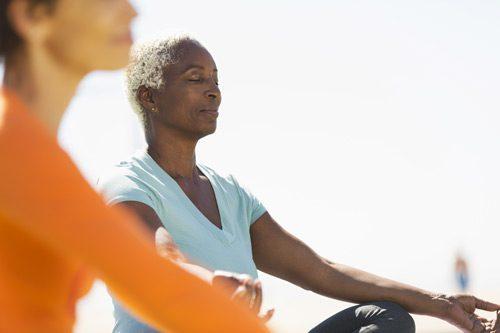 senior age Black woman meditating in the lotus position - styles of meditation