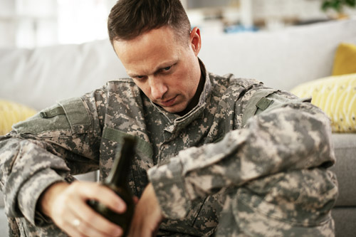 man in camoflauge at home sitting on floor drinking a bottle of beer - veterans and addiction