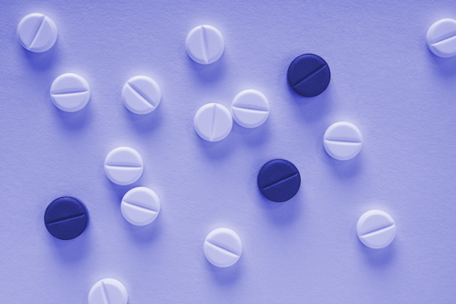 scored white and purple tablets on purple background - morphine addiction
