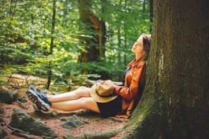 young woman in hiking clothes sitting, leaned against a large tree in a coniferous forest - stress in recovery